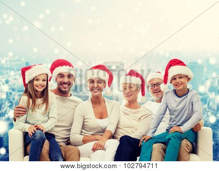 family, happiness, generation, holidays and people concept - happy family in santa helper hats sitting on couch over snowy city background