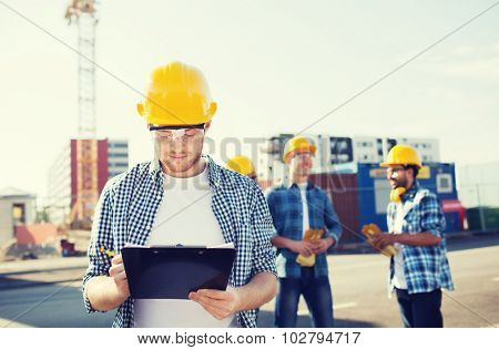 business, building, teamwork and people concept - group of builders in hardhats with clipboard outdoors
