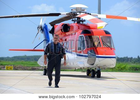 caucasian offshore helicopter pilot is walking and smiling beside of helicopter at apron