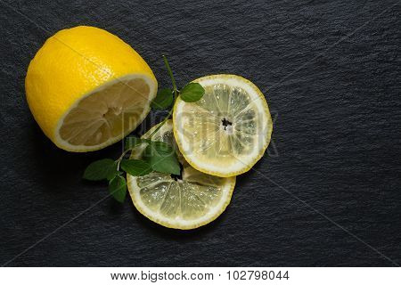 Slices And Half A Lemon With A Sprig Of Mint On A Slate Blackboard