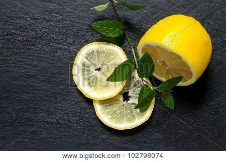 Cut Lemon With A Sprig Of Mint On A Slate Blackboard