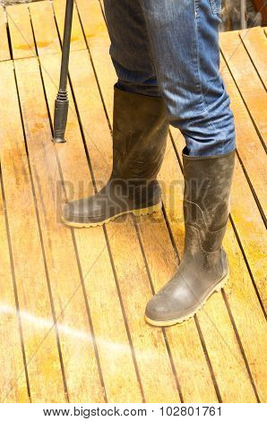 Man Wearing Rubber Boots Using High Water Pressure Cleaner On Wooden Terrace Surface