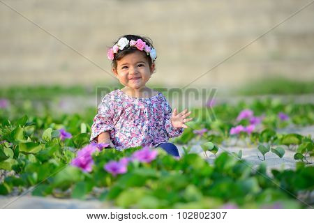 Smiling baby girl wearing colorful suit and flower hat is playing among flower on beach