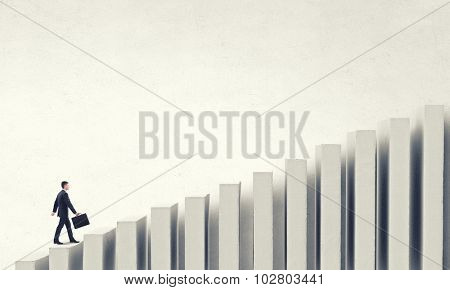 Young businessman walking up on bars staircase representing success concept