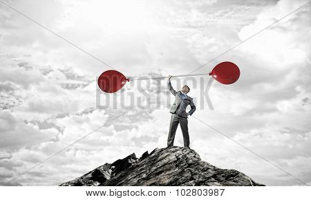 Confident businessman lifting above head barbell with balloons
