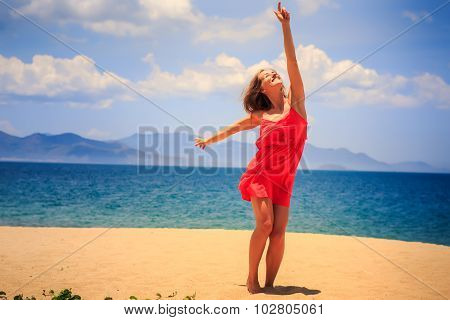 Blond Girl In Red Stands On Sand Beach Lifts Hand Points To Sun