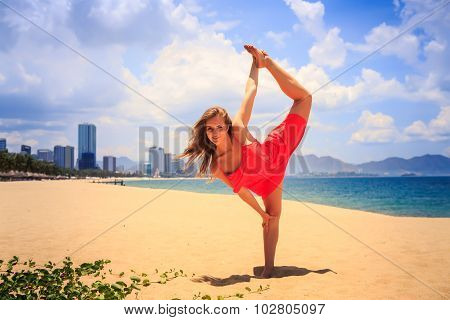 Blond Girl In Red Stands In Gymnastic Position Leg Scale On Sand