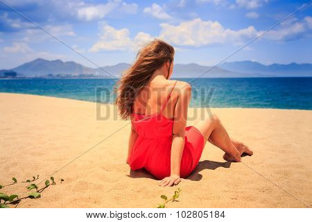 Girl In Red With Naked Back Sits On Sand Looks At Sea