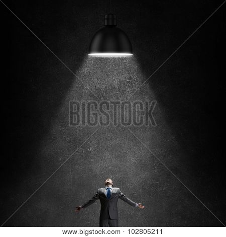 Businessman with hands spread apart standing in lamp light from above