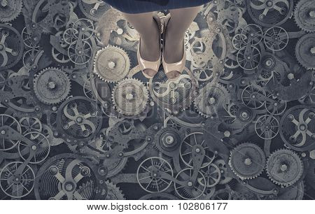 Top view of businesswoman standing on floor of gears