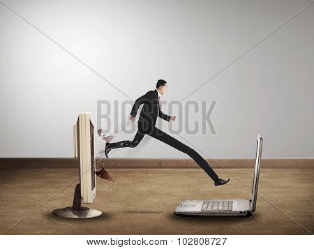 Business Man With Long Leg Out From Computer Desktop To Laptop