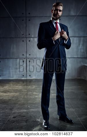 Young handsome businessman with beard in black suit standing on wall background.