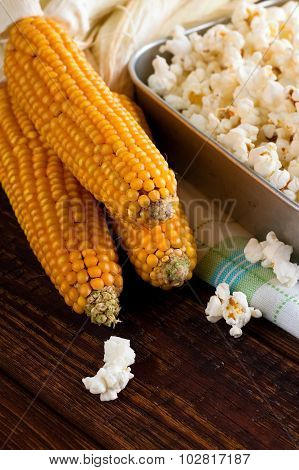 Three Corncobs Next To Pan With Fresh Popcorn