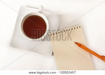 A notepad with a bright pen and a cup of tea on a white background with a place for text