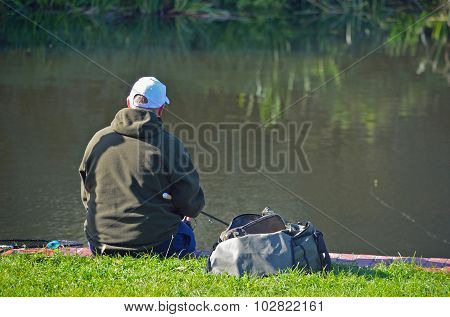 Fisherman sitting on the bank of the river Ouse.