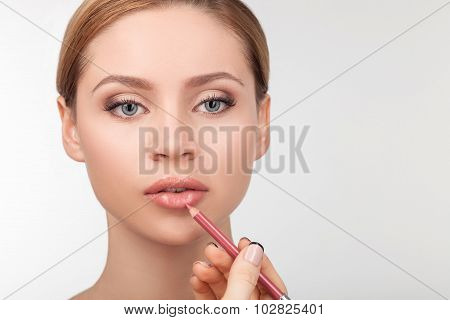 Attractive young girl is having her face pained