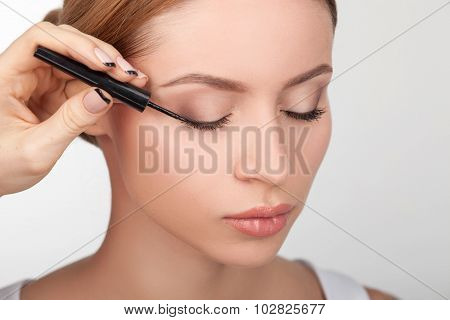 Skilled young beautician is doing make-up for girl