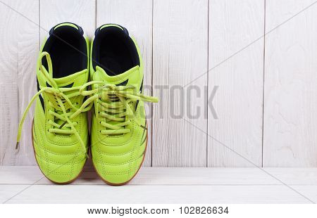 pair of sport shoes on a white wooden wall