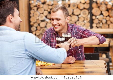 Handsome young guys are swigging lager in bar