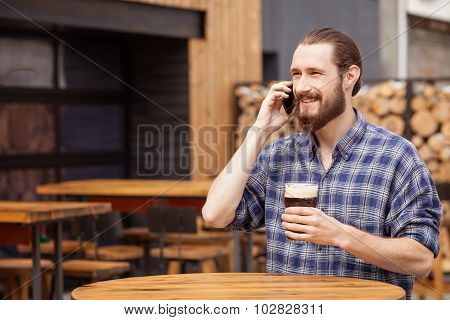 Handsome bearded guy is communicating on telephone in pub