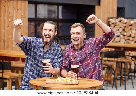 Handsome two male friends are resting in bar