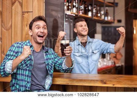 Cheerful young guy and bartender in sport pub