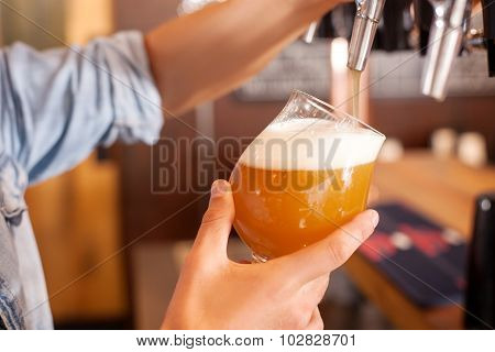 Cheerful young bartender is pouring lager in pub