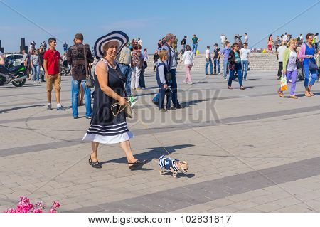 Cute pair - woman with her small dog on the Dnepr river embankment