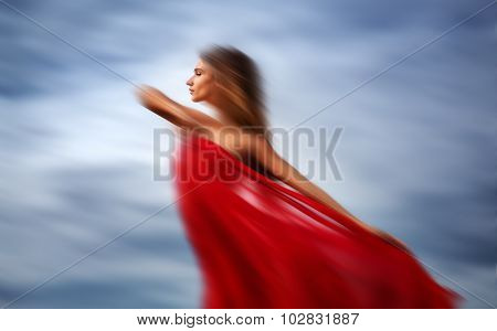 Blurred Woman On A Beach With Red Fabric