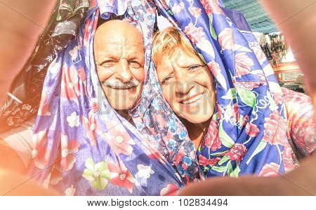 Senior Happy Couple Taking A Selfie At The Week Clothes Market Traveling Around The World - Concept