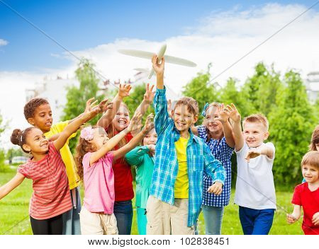 Kids reaching after white airplane toy with arms