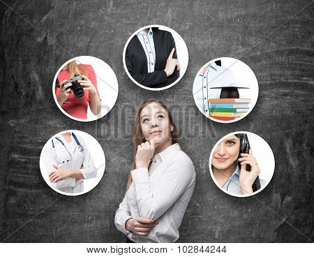 A Beautiful Young Lady In A Formal Shirt Is Thinking About Different Professions. Black Chalkboard A