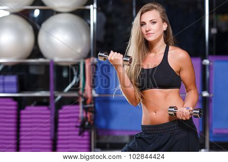 Nice young girl wearing in black top and breeches posing with dumbbells on the sport equipment background in the gym waist up