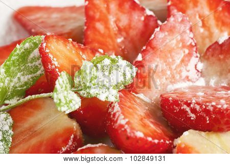 detail of halved strawberries sprinkled with icing sugar