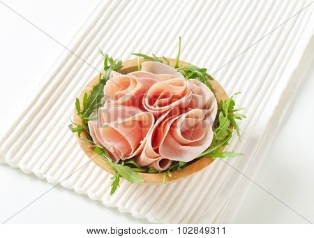 bowl of fresh arugula salad with sliced ham on white place mat