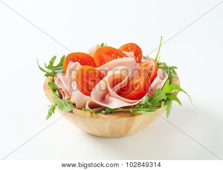 bowl of fresh arugula salad with sliced ham and halved tomatoes on white background