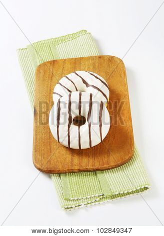 ring donuts with vanilla and chocolate glaze on wooden cutting board and green place mat