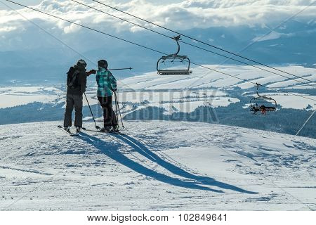 Skiers couple looking on the winter mountains in sun day.