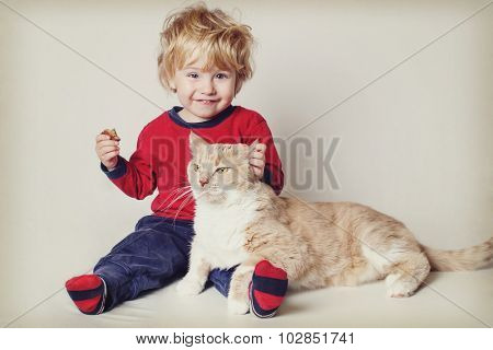 Smiling toddler boy with his pet cat. Vintage toned image. Focus on cat's face.