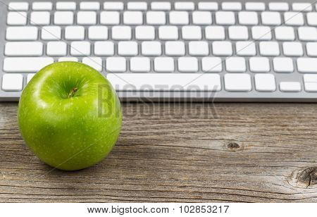 Healthy Green Apple With Keyboard On Rustic Wooden Desktop