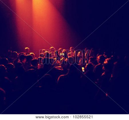 a crowd of people at a concert with one holding a cell phone taking a photo toned with a retro vintage instagram filter effect app or action