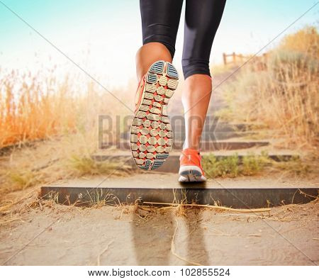 a woman with an athletic pair of legs going for a jog or run during sunrise or sunset up stairs in the mountains - healthy lifestyle concept for urban living