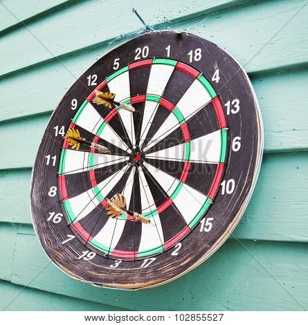 an old weathered dart board on the side of a house with darts in it