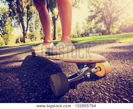 a wide angle shot of a skateboarder riding on a road with grass and trees in the background during sunrise or sunset toned with a retro vintage instagram filter app or action effect