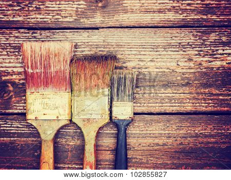a set of paintbrushes in a row on a stained wooden background toned with a retro vintage instagram filter app or action effect