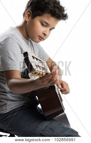 Vertical image of cute little boy playing guitar isolated on white background.