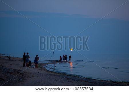 group of night fishermen launching paper lantern