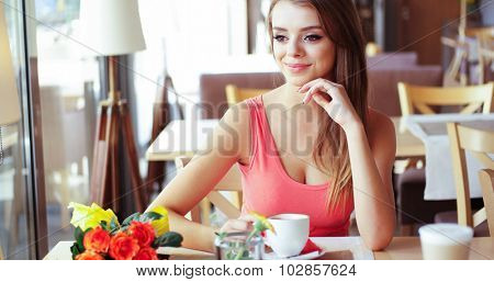 Portrait of Smiling Young Woman with Mug of Coffee Sitting in Sunny Window Seat of Trendy Cafe Restaurant