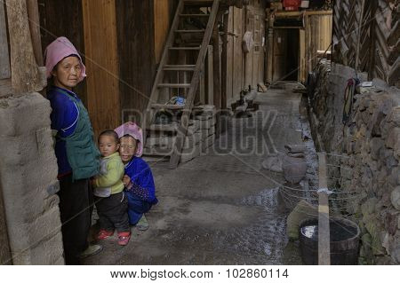 Two Chinese Women And Child, In Courtyard Of Their House.