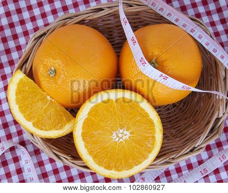 A Wicker Basket Full Of Fresh Orange Fruits With Centimeter On Tablecloth